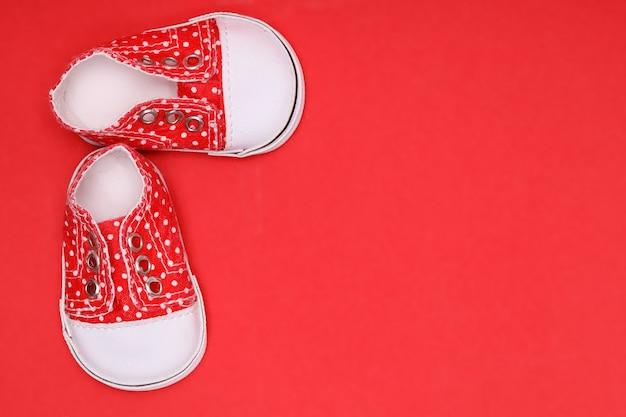 Sapatos de bebê vermelhos com bolinhas brancas em um fundo vermelho
