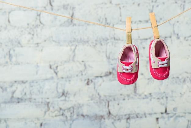 Sapatos de bebê vermelhos em uma corda contra uma parede de tijolos brancos.