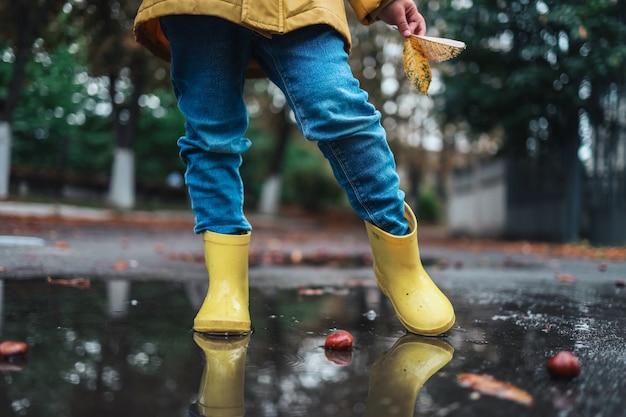 Sapatos de borracha amarela na poça depois de chover. folhas que caem. conceito da temporada de outono.