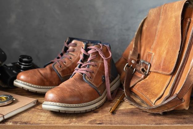 Sapatos de botas vintage para viagem e bolsa de couro na mesa de madeira, com textura de fundo de parede