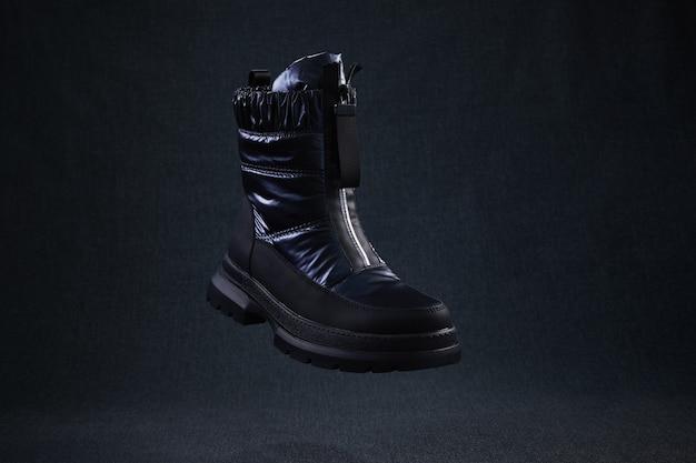 Sapatos de caminhada pretos de inverno levitam no ar. sapatos femininos elegantes modernos para caminhadas off-road.