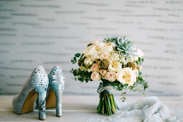 Sapatos de camurça cinza com salto de pele de cobra ao lado de um buquê de noiva com fitas de seda