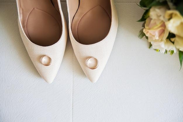 Sapatos de casamento bege bonito e anéis de casamento