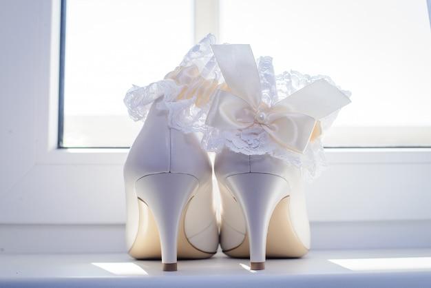 Sapatos de casamento branco da noiva e liga pela janela