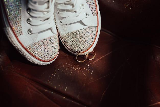 Sapatos de casamento branco e anéis de casamento no quarto da noiva.