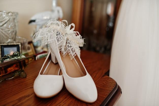 Sapatos de casamento branco elegante na manhã da noiva.