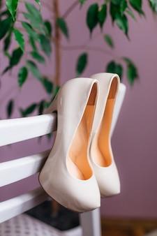 Sapatos de casamento brancos com salto são pendurados em uma cadeira branca antes que a noiva os coloque para a cerimônia de casamento
