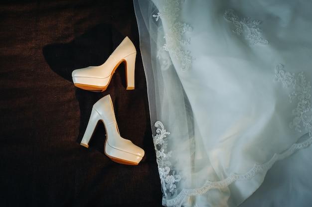 Sapatos de casamento brancos e vestido em fundo preto