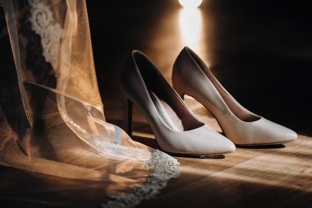 Sapatos de casamento brancos em pé no campo perto do vestido