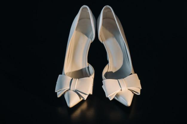 Sapatos de casamento brancos em uma superfície preta.