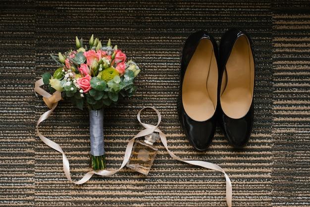 Sapatos de casamento, buquê de rosas e eucalipto, uma jarra de água de toalete