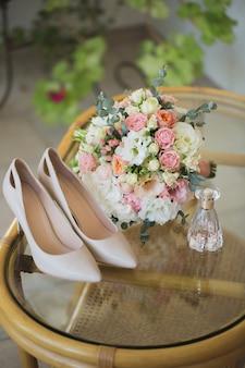 Sapatos de casamento com buquê de flores e perfume