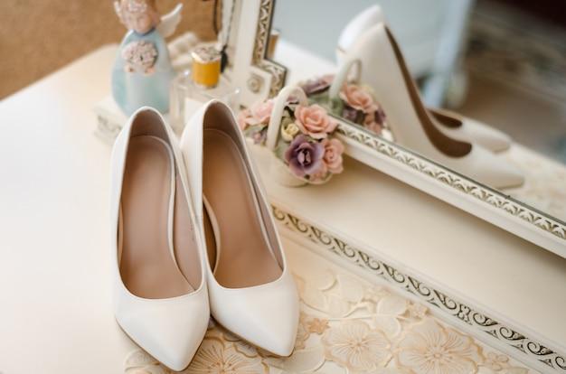 Sapatos de casamento com salto alto e borda de ouro. sapatos de noiva estão perto do espelho