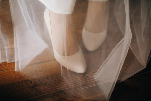 Sapatos de casamento da moda. sapatos de mulher no véu de noiva.