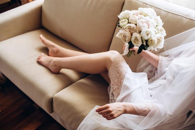 Sapatos de casamento da noiva com um buquê de peônias e outras flores na poltrona.