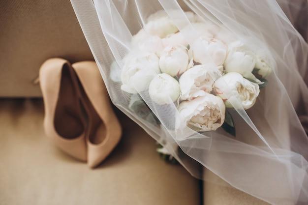 Sapatos de casamento da noiva com um buquê de peônias e outras flores.