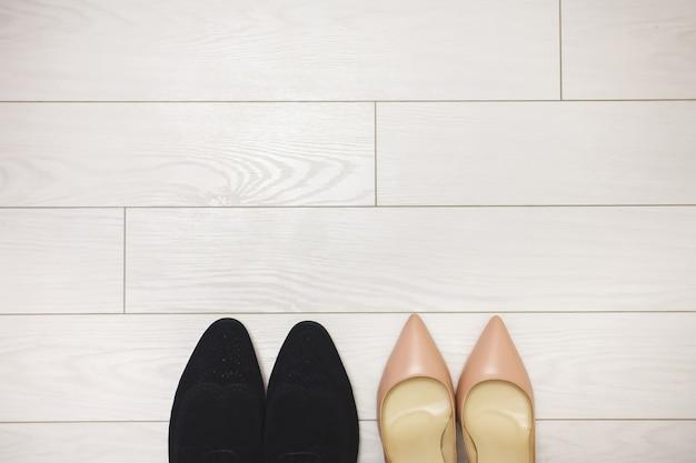 Sapatos de casamento da noiva e do noivo. mesa. pisos.