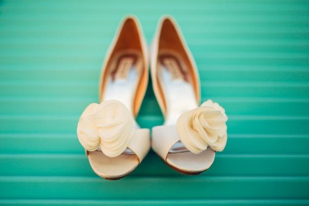 Sapatos de casamento da noiva em um fundo azul de madeira