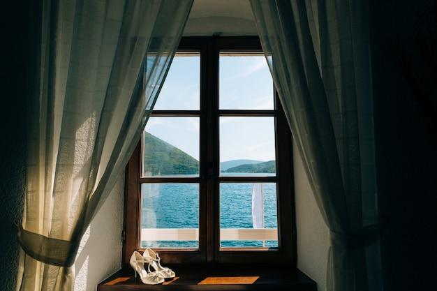 Sapatos de casamento da noiva em uma janela