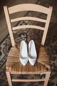 Sapatos de casamento das mulheres na cadeira