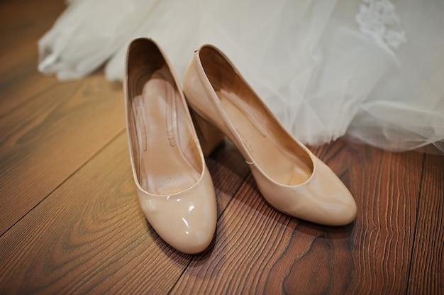 Sapatos de casamento de cor creme no chão de madeira