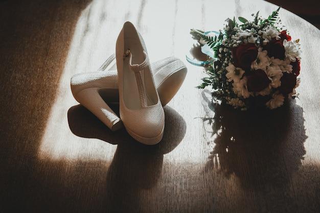 Sapatos de casamento de couro branco de salto alto e um buquê de noiva no chão de madeira sob as luzes do sol.