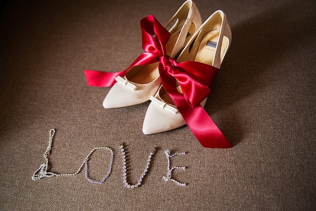 Sapatos de casamento de jóias amarrados com um laço vermelho
