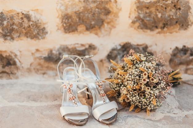 Sapatos de casamento de uma noiva em um fundo de pedra e um buquê de noiva branco