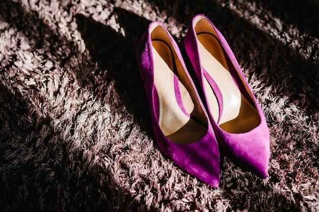 Sapatos de casamento de veludo roxo feminino em fundo bege. acessórios de noiva. vista do topo.
