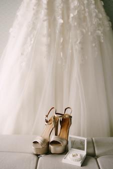 Sapatos de casamento dourados ao lado de acessórios de noiva com um vestido de noiva pendurado no bacground