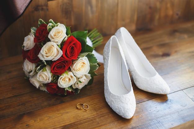 Sapatos de casamento e buquê de rosas vermelhas e brancas