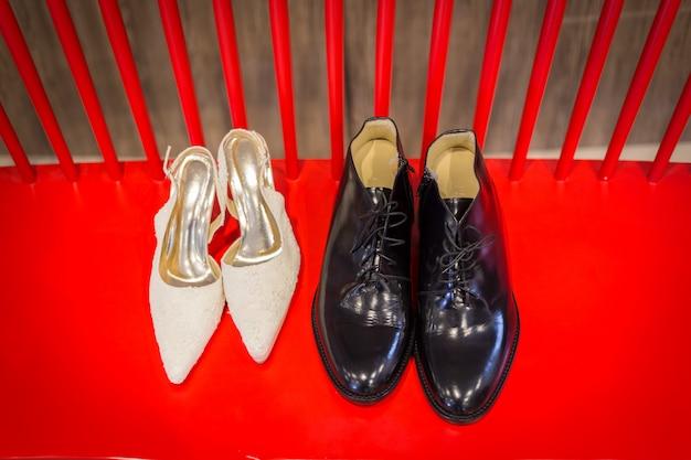 Sapatos de casamento e buquê em uma cadeira vermelha para a cerimônia de casamento