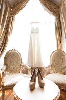 Sapatos de casamento e vestido de noiva branco em quarto luxuoso