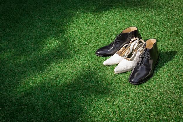 Sapatos de casamento feminino e masculino na grama verde para a cerimônia de casamento