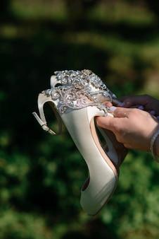 Sapatos de casamento nas mãos de noivas