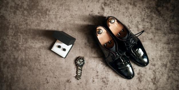 Sapatos de casamento, relógio e abotoaduras