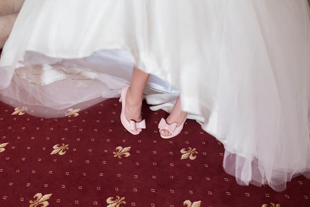 Sapatos de casamento roxos nos pés da noiva