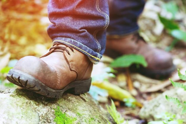 Sapatos de close-up de viajante turista caminhante, caminhantes de turista homem caminhando na trilha de passos da floresta em uma madeira com luz do sol.