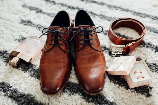 Sapatos de couro marrom, cinto, perfume e anéis de ouro.
