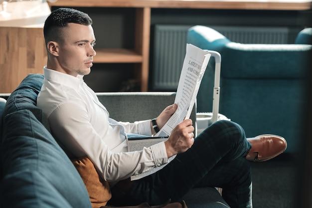 Sapatos de couro marrom. homem de negócios elegante e bonito usando sapatos de couro marrom lendo notícias em quarto de hotel