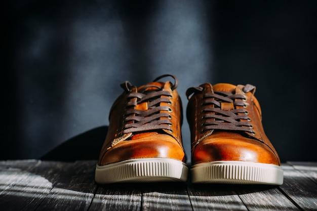 Sapatos de couro marrom masculino com cadarços no fundo escuro de madeira