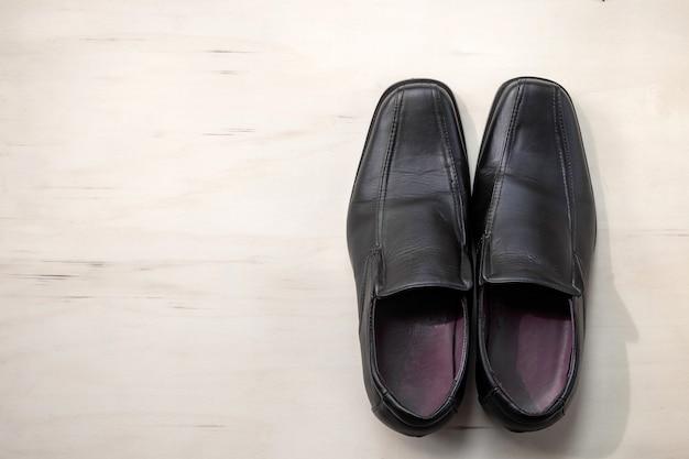 Sapatos de couro masculino em fundo de madeira