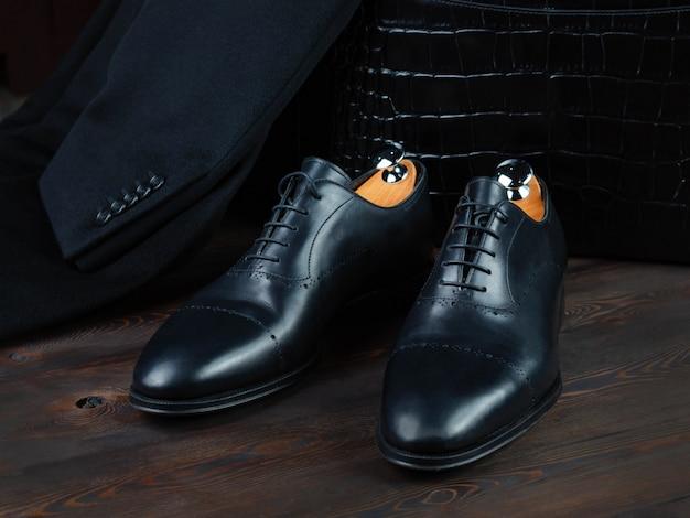 Sapatos de couro masculino preto sobre um fundo de uma carteira de couro de crocodilo e uma jaqueta