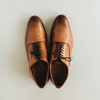 Sapatos de couro masculinos em superfície pastel