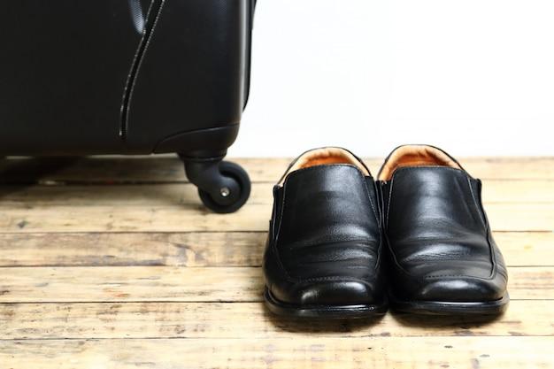 Sapatos de couro preto e bolsa de viagem de bagagem na mesa de madeira