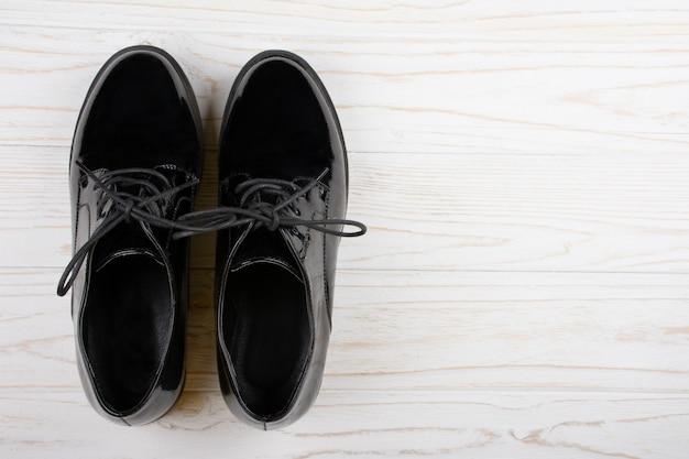 Sapatos de couro preto sobre um fundo branco de madeira