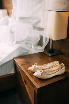 Sapatos de creme da noiva em verde sobre uma mesa de madeira