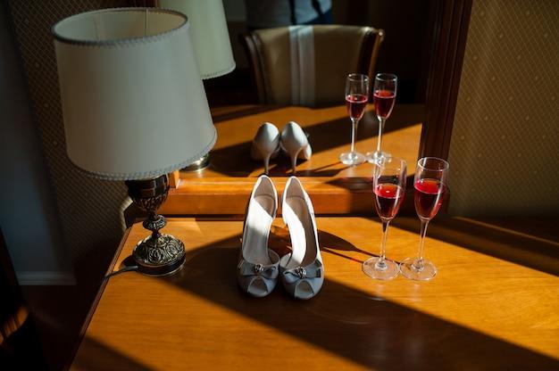 Sapatos de dama de honra e taças de champanhe.