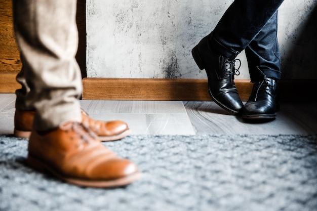 Sapatos de dois homens em pé no chão, close-up