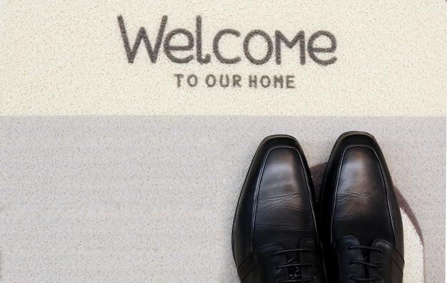 Sapatos de empresário na esteira de boas-vindas cinza